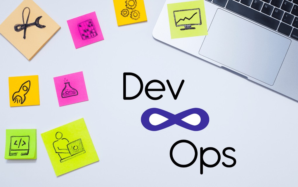 white table with a laptop and sticky notes on it reading DevOps
