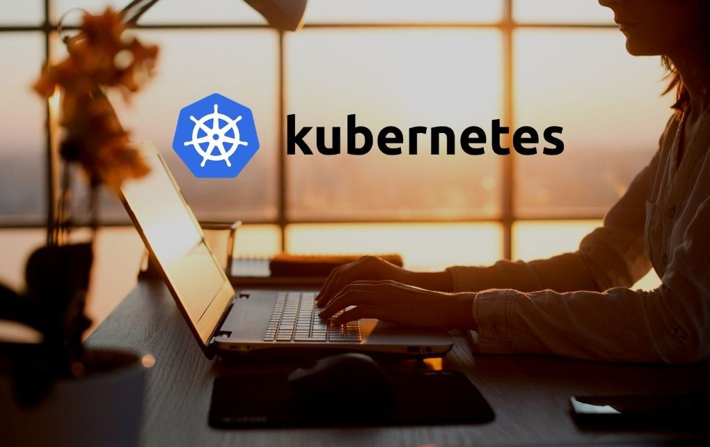 kubernetes logo and woman working on laptop