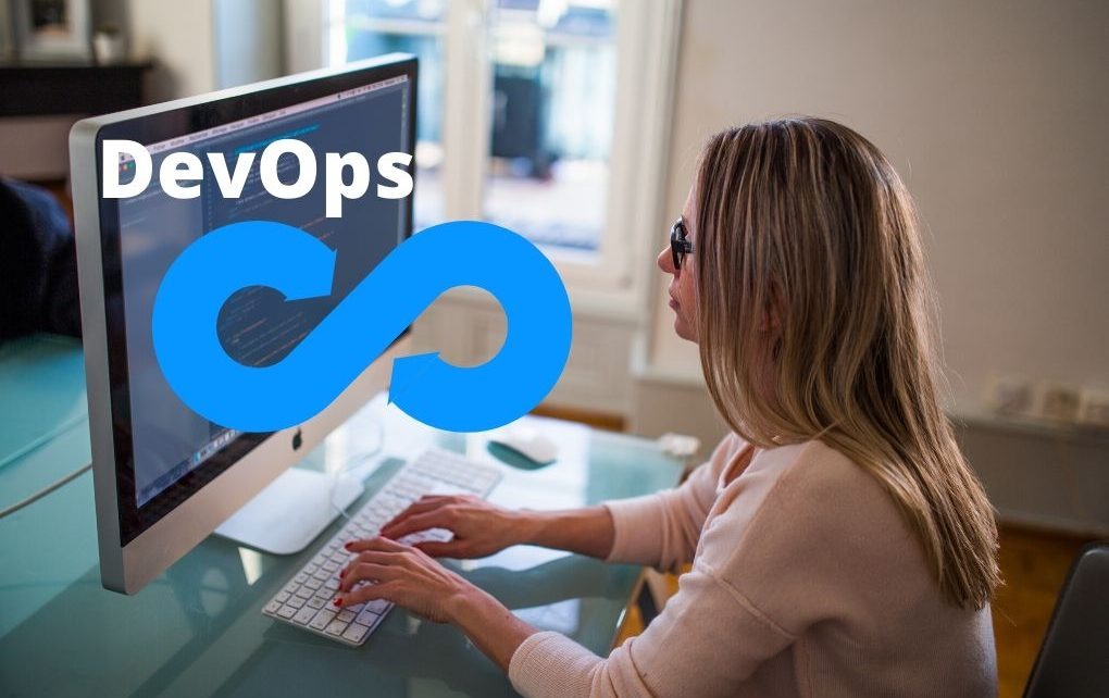 Devops symbol and a woman typing code on a computer